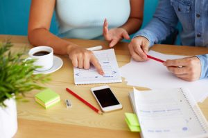 Employees Discuss Content Marketing With Notepad and Notebook
