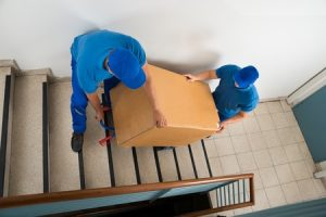 Moving Company Workers Carrying Box on Stairs