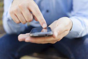 Man Browsing Phone For Plumber Social Media Marketing