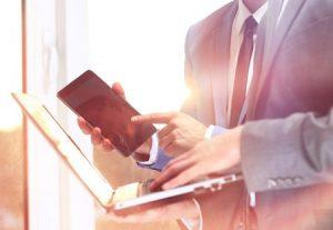 Businessman Checks Website Management on Laptop and Computer